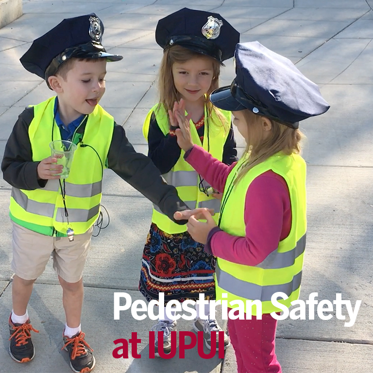 Children high-fiving one another on a job well done protecting pedestrians.