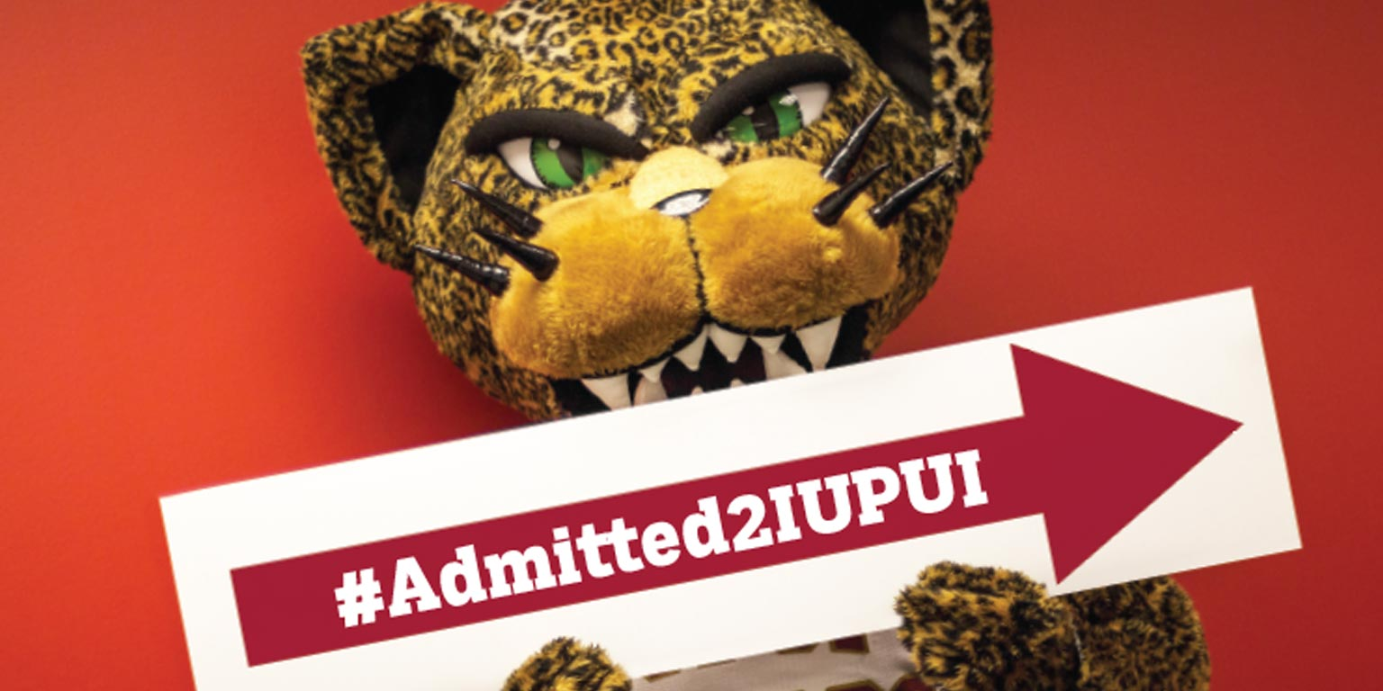 Jaguar mascot holds #Admitted2IUPUI promotional sign.