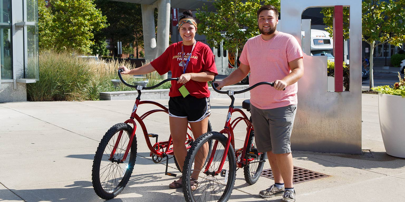 The winners, Brandon Slaton and Taylor Hobbs, pose with the red bikes they won.